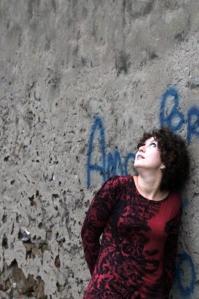 ragazza riccia appoggiata al muro